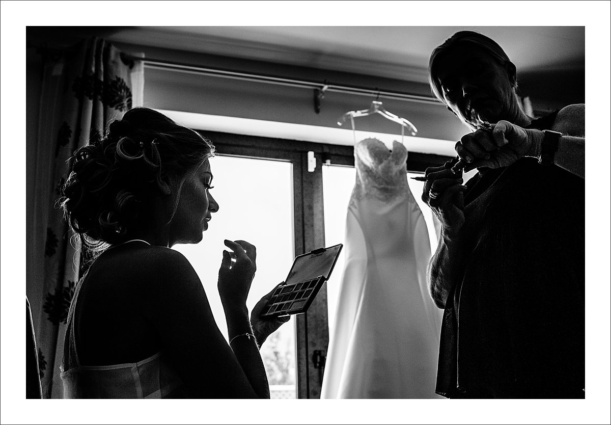 a silhouette photo of a bride having her makeup done in Marbella