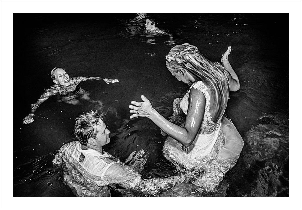 bride and groom jump in the pool
